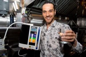 "New York - July 22, 2015: For Features - Canalp ""Jon"" Caner holds a LeveLuk sd water iodizer made by Enagic in the Kitchen of Mundo restaurant he co-owns with Guillermo ""Willie"" Lucerofabbi located in the Paper Factory Hotel at 37-06 36th Street in Long Island City, NY.   The LeveLuk sd water iodizer is used to raises the Ph balance of the water run through it. The pair say this process enriches the mineral content and raises the antioxidant levels of the water. This purified water is used extensively in the restaurant for cooking, making drinks and even used to make the ice cubes.  Credit: Lorenzo Ciniglio/Freelance"
